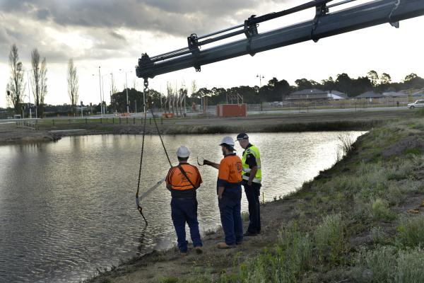 Police and workers from Plunkett Crane Trucks search for the car in the lake in Officer on Tuesday evening.