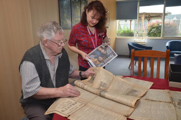 Resident of Pakenham Millhaven Lodge Ron, looked through the 100-year-old newspaper with worker Raema.  Pictures: DONNA OATES 125048