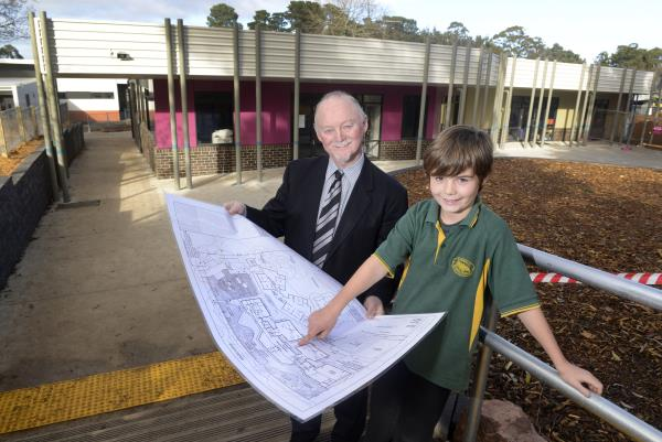 School principal Mark Carver with 10-year-old student James pointing at plans with the newly completed administration wing behind.  125334 Pictures: ROB CAREW