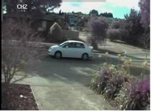 The vehicle is described as a late model white Nissan Tiida sedan with a rear spoiler.