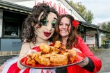 Mascot 'Sally Burger' with the real-life burger-flipping Sally from Sally's Big Ass Burgers holding a steaming plate of dim sims ahead of their upcoming scoff competition.